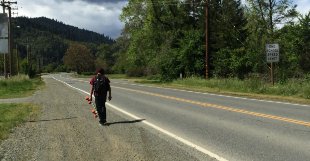 Young man with skateboard on Hoopa Valley Indian Reservation road