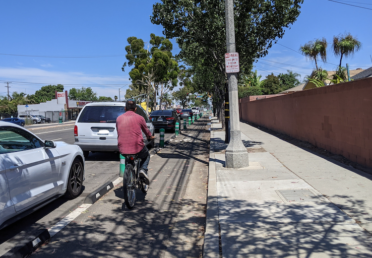Man bicycling in a bike lane in North Long Beach, CA