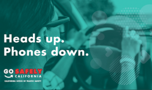 Pedestrian safety tip for drivers to have heads up and phones down with image of female driver with both hands on the wheel while driving