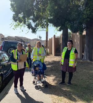 A group of people wearing high visibility vests are pictured during a walking audit, there is a child in a stroller in the middle of the photo