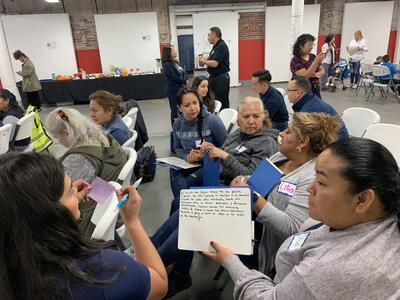 A group of people are huddled together while sitting, one person is pictured holding a piece of paper to discuss potential safety projects for the neighborhood