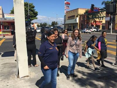 Karla Vilchys walking hand in hand with her child during the South LA CPBST Site Visit.